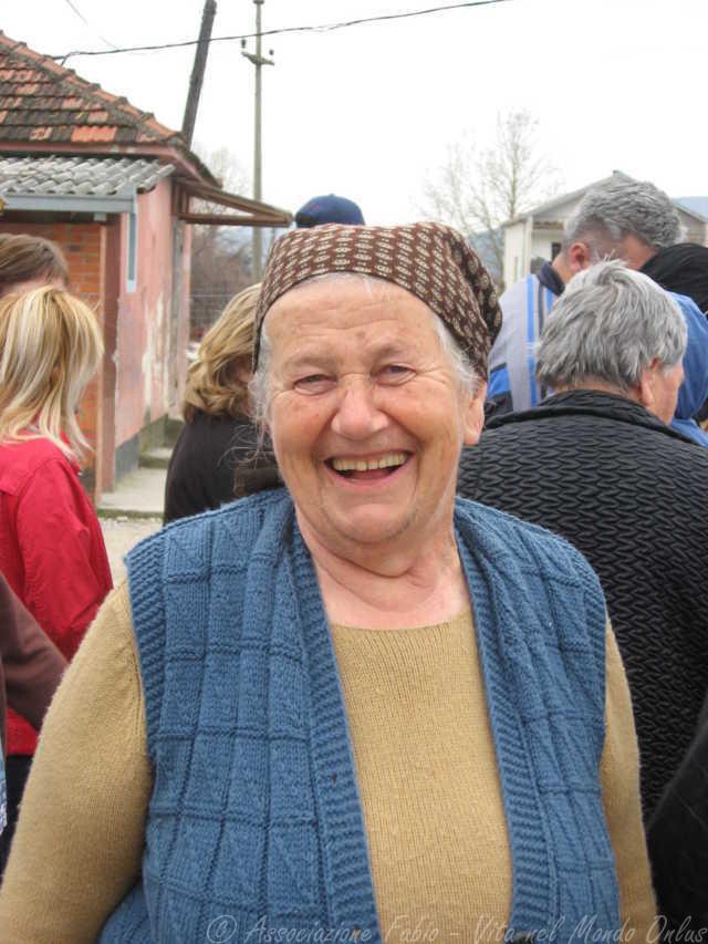 Una signora anziani sorride, in fila per ricevere il pacco famiglia preparato dall'Associazione